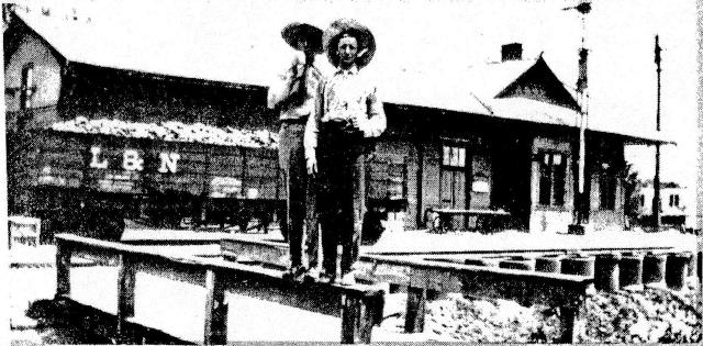 Two young men on railroa bridge with depot as backdrop.